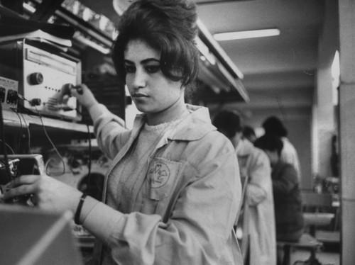 Woman operating a television set manufacturing plant (circa 1963).