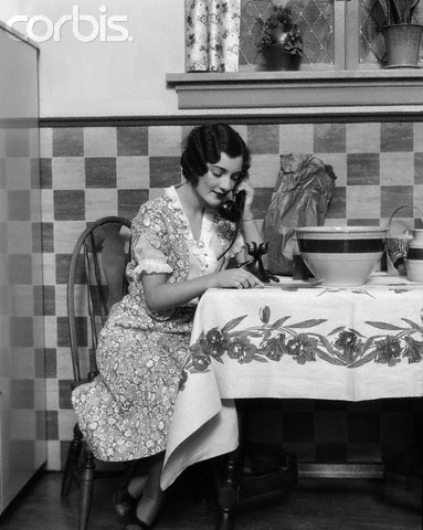 1920s Woman Sitting At Kitchen Table With Table Cloth While On Phone